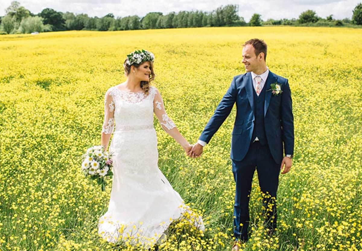 Bride and groom in field of yellow flowers