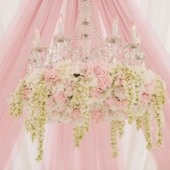 Pink chandelier inside wedding marquee